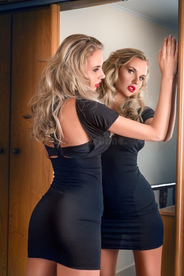 Jeune femme regardant dans le miroir photo stock