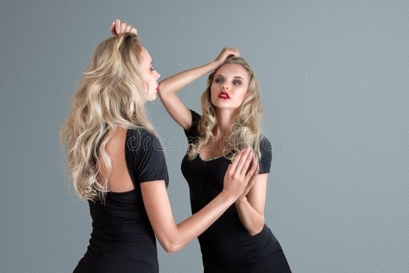 Jeune femme regardant dans le miroir image stock