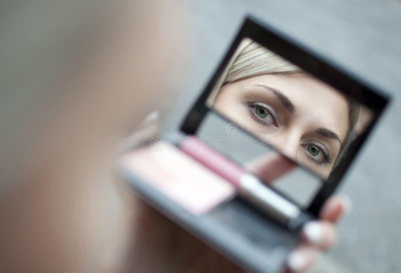 Jeune femme regardant dans le miroir cosmétique photo libre de droits