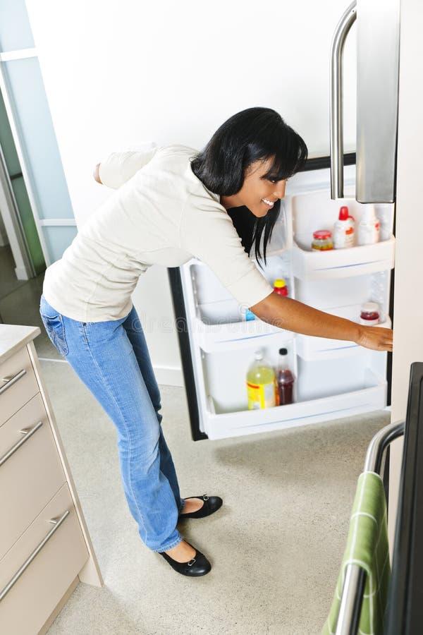 Jeune femme regardant dans le réfrigérateur photographie stock