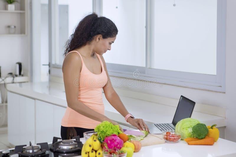 Jeune femme regardant des recettes sur un ordinateur portable image libre de droits