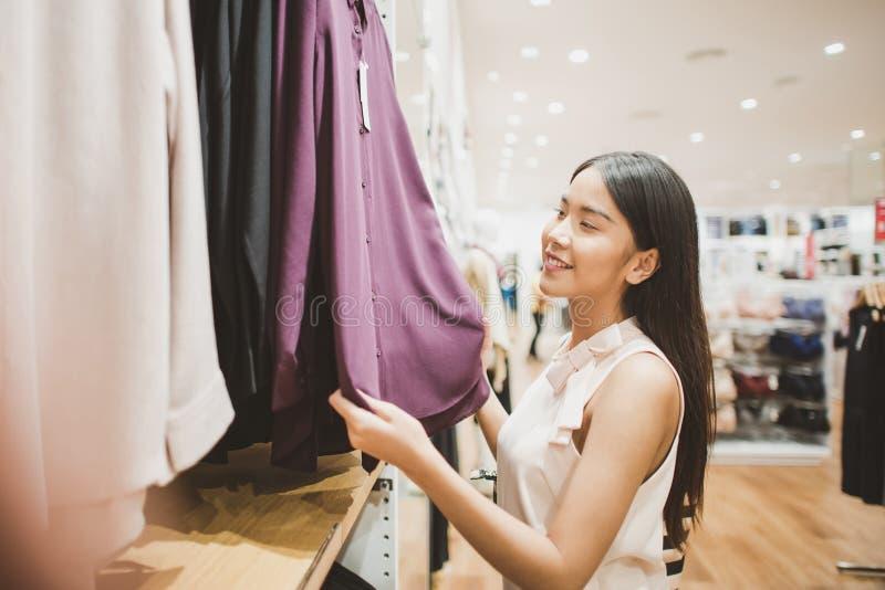 Jeune femme regardant des vêtements accrochant sur le rail à l'intérieur de la boutique d'habillement images stock