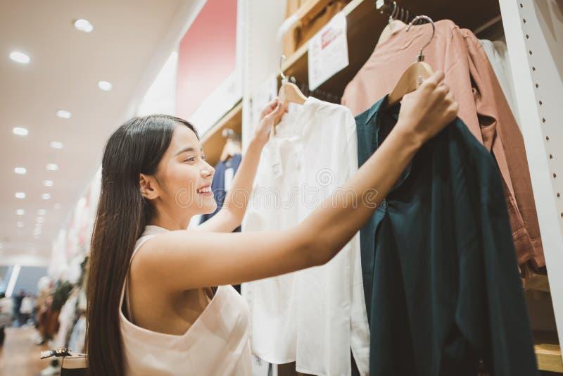 Jeune femme regardant des vêtements accrochant sur le rail à l'intérieur de la boutique d'habillement photo libre de droits