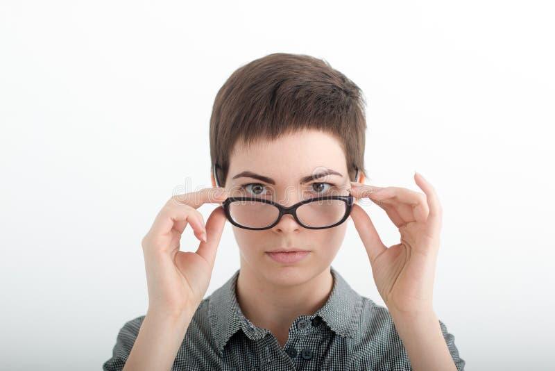 Jeune femme regardant fixement au-dessus de ses verres Lunettes de port de professeur strict image libre de droits
