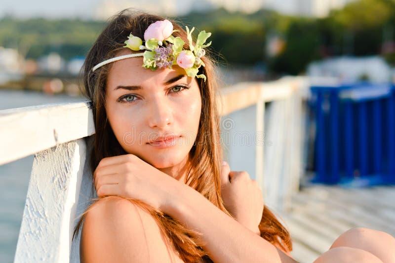 Jeune femme regardant l'appareil-photo appréciant le jour ensoleillé sur la plage photo libre de droits