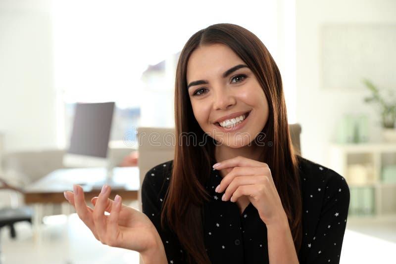 Jeune femme regardant la cam?ra et employant la causerie visuelle photo libre de droits