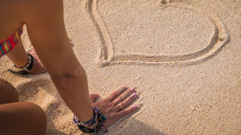 Jeune femme regardant la forme de coeur de Drawed en sable sur la plage, Bali photos stock