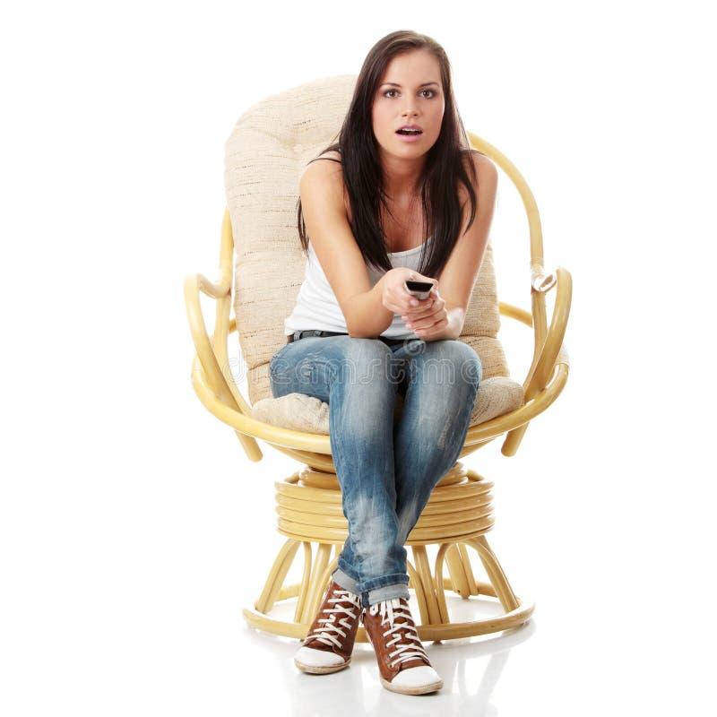 Jeune femme regardant la TV - effrayée photos stock