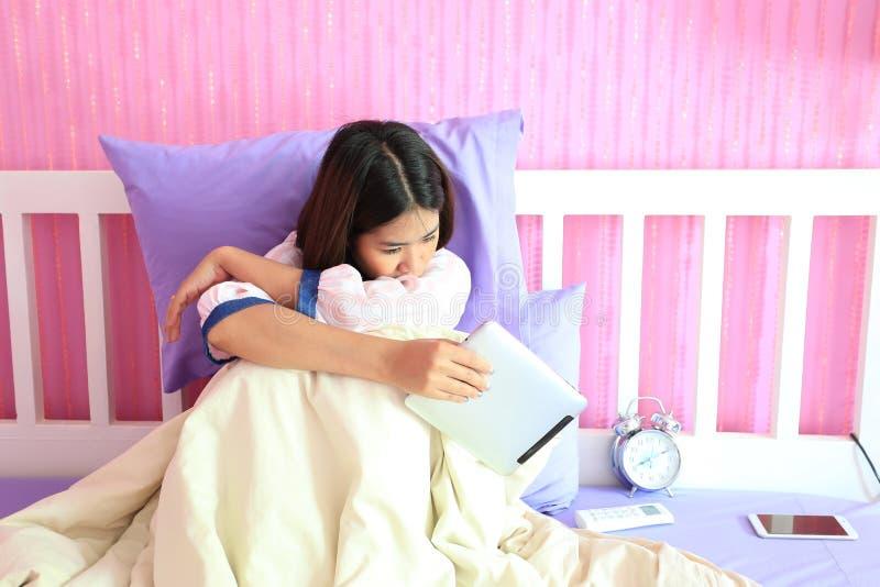 Jeune femme regardant le dispositif intelligent de comprimé avec sentiment triste et photographie stock libre de droits