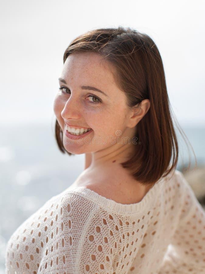Jeune femme regardant le sourire d'appareil-photo images stock