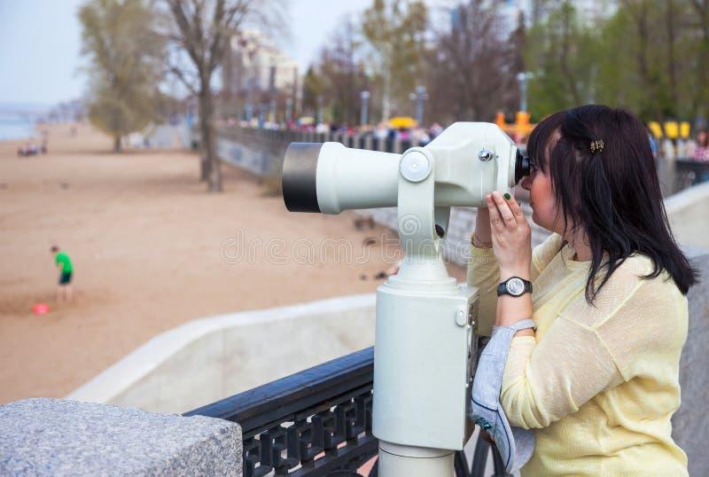 Jeune femme regardant par le binoculaire à jetons photos libres de droits