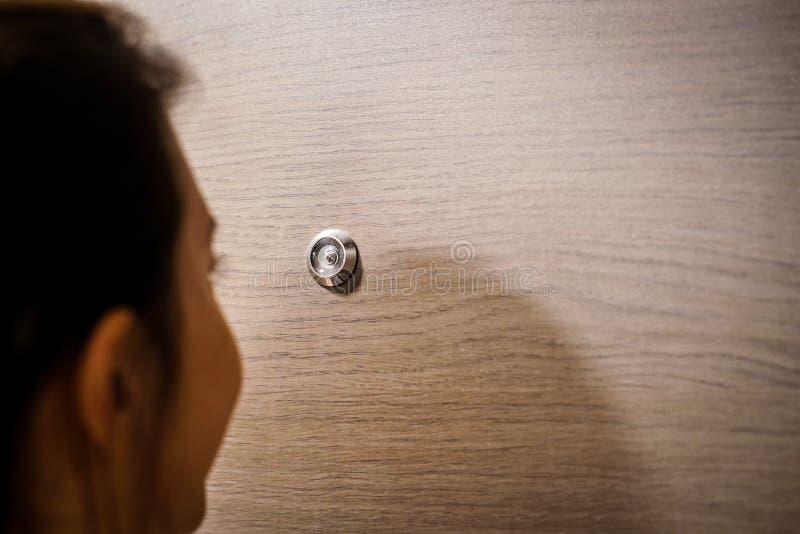 Jeune femme regardant par le trou de son entrée principale images stock