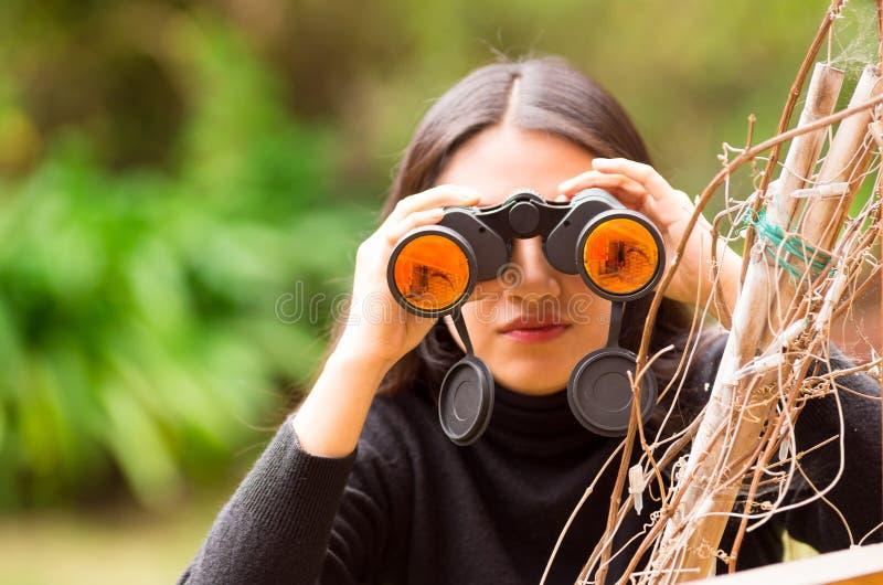 Jeune femme regardant par les jumelles noires dans la forêt à un arrière-plan brouillé photo libre de droits