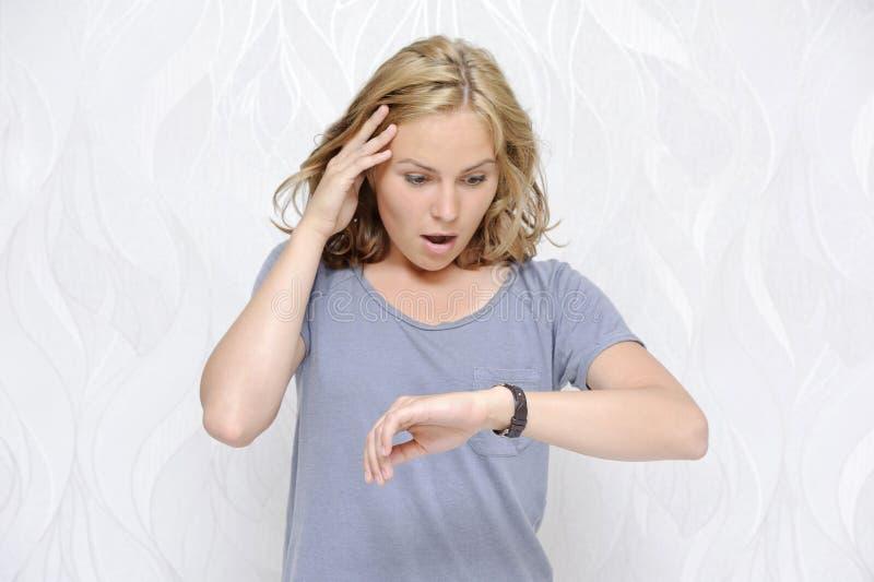 Jeune femme regardant sa montre étant en retard photo stock
