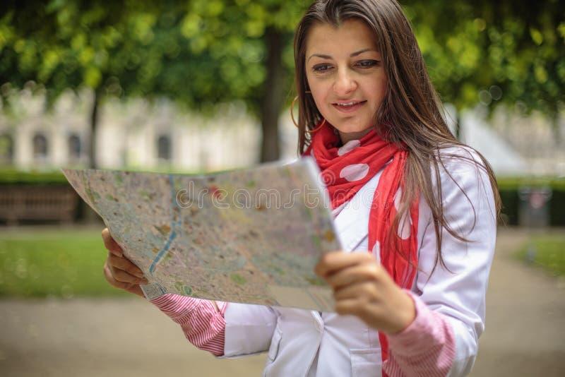 Jeune femme regardant sur la carte le parc Paris, France de ville images stock