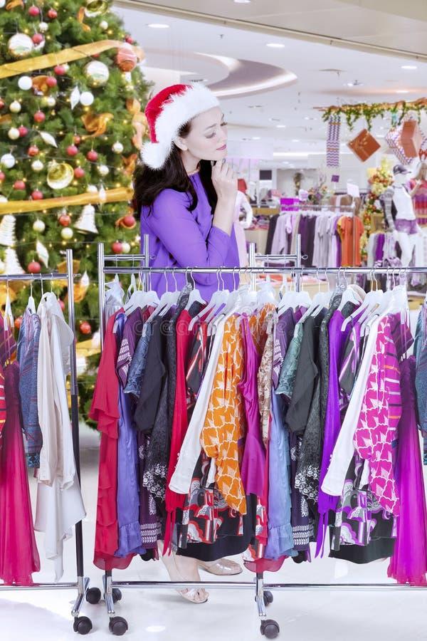 Jeune femme regardant une robe pour des cadeaux de Noël image stock