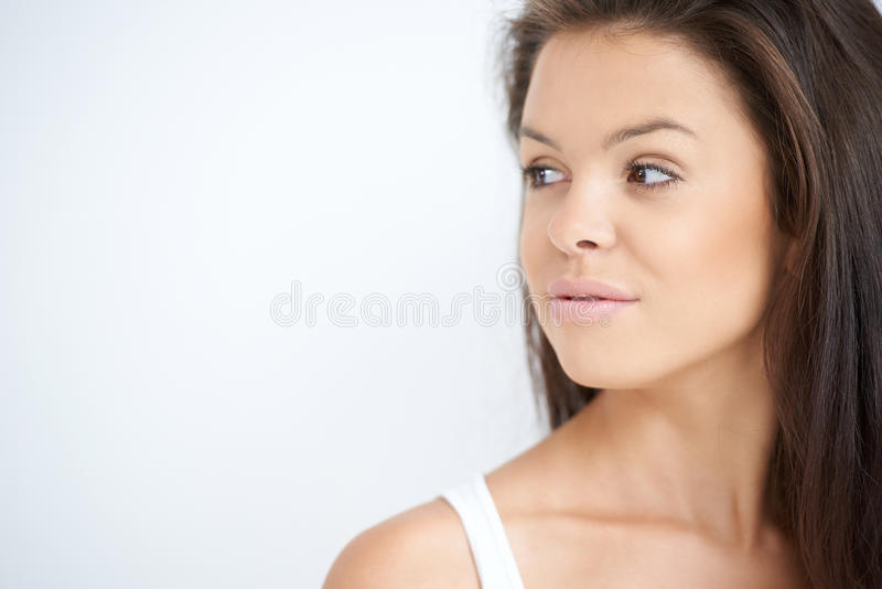 Jeune femme regardant vers sa droite sur le blanc photo libre de droits