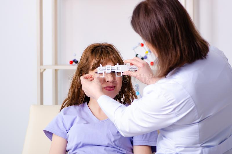 Jeune femme rendant visite à l'oculiste féminin de docteur photos stock