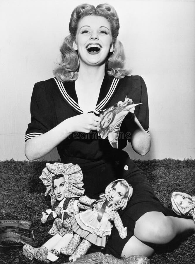 Jeune femme reposant et coupant les poupées de papier (toutes les personnes représentées ne sont pas plus long vivantes et aucun  image libre de droits