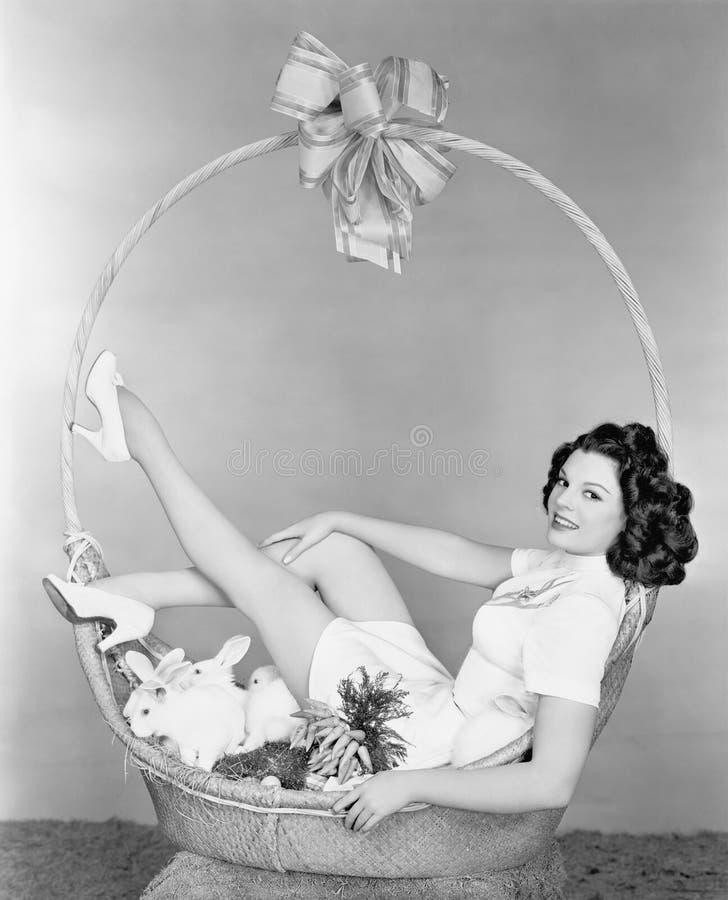 Jeune femme, ressemblant à un présent, se reposant dans le panier de cadeau avec des lapins (toutes les personnes représentées ne image stock