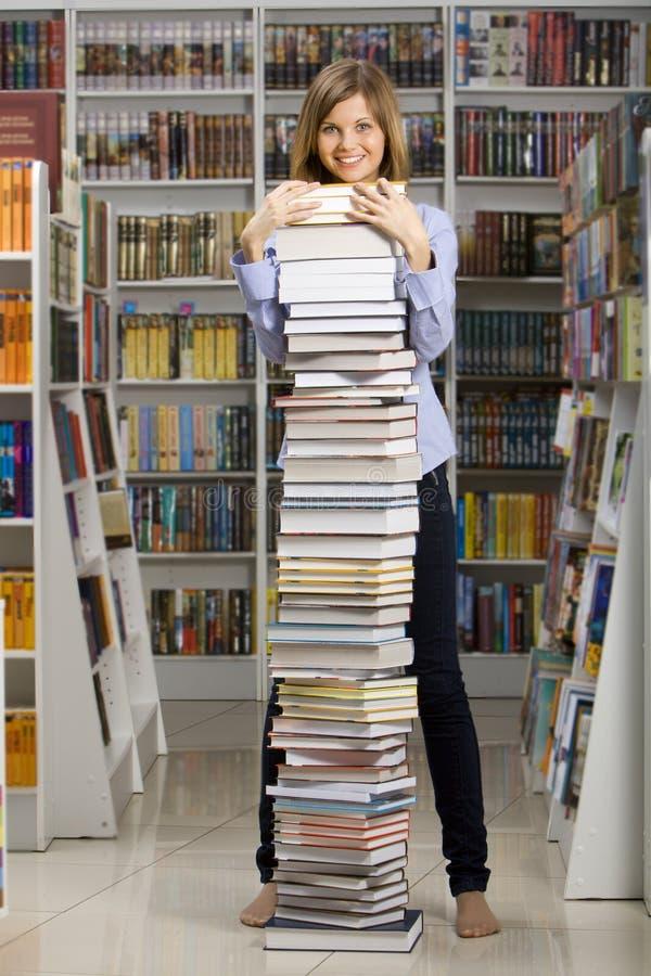 Jeune femme restant avec la grande pile de livres photographie stock