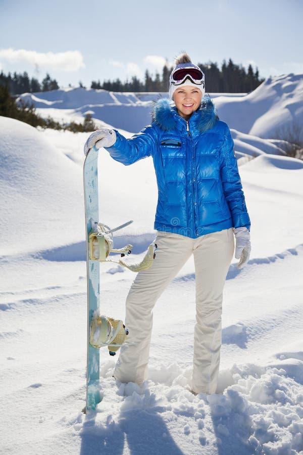 Jeune femme restant avec le surf des neiges dans son non-et et sourire images libres de droits