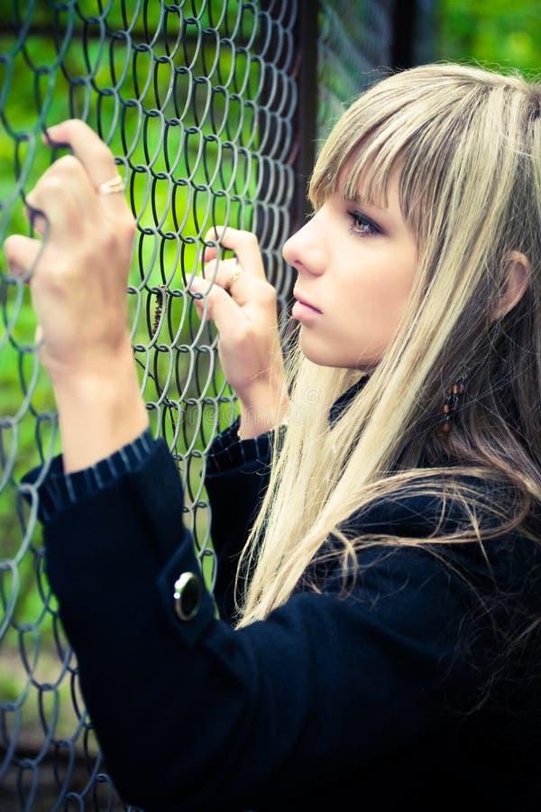 Jeune femme retenant en fonction la frontière de sécurité photo stock