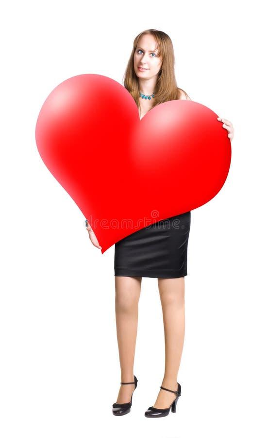 Jeune femme retenant la grande forme de coeur dans des mains photo libre de droits
