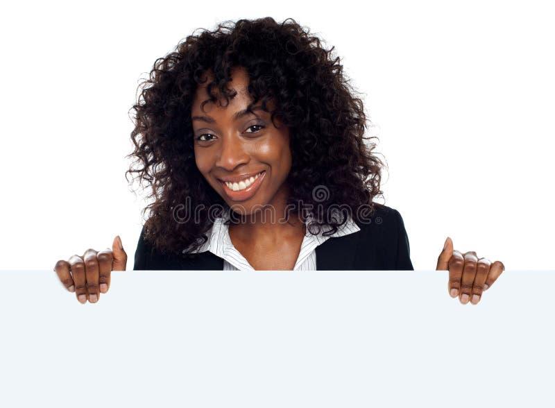 Jeune femme retenant la plaquette blanche blanc photos stock