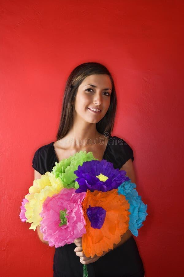 Jeune femme retenant les fleurs de papier. D'isolement photographie stock libre de droits