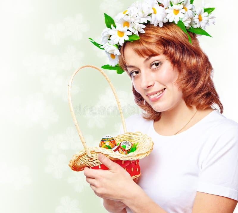Jeune femme retenant un panier avec des oeufs de pâques photo stock