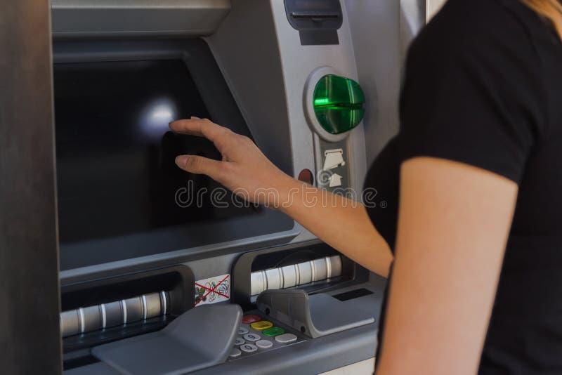 Jeune femme retirant l'argent liquide d'un distributeur automatique de billets image stock