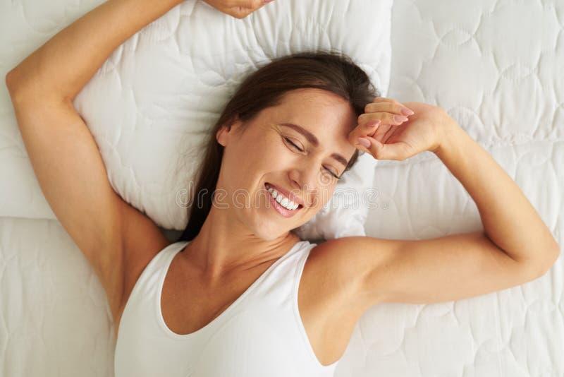 Jeune femme riant et s'étirant dans le lit après un bon repos photographie stock libre de droits