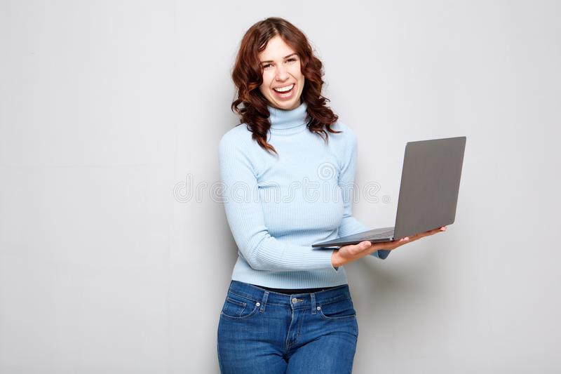 Jeune femme riant et tenant l'ordinateur portable sur le fond gris photos stock
