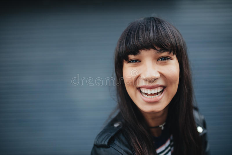 Jeune femme riant sur le fond gris images stock