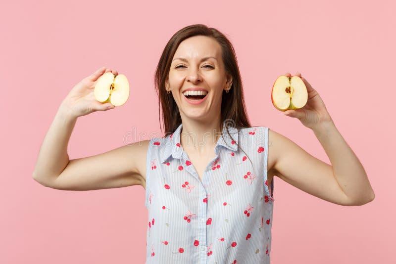 Jeune femme riante dans des vêtements d'été se tenant dans des halfs de mains du fruit mûr frais de pomme d'isolement sur le past photographie stock libre de droits