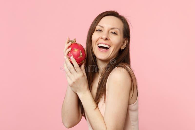 Jeune femme riante dans des vêtements légers tenant le pitahaya mûr frais, fruit du dragon d'isolement sur le fond en pastel rose photo libre de droits