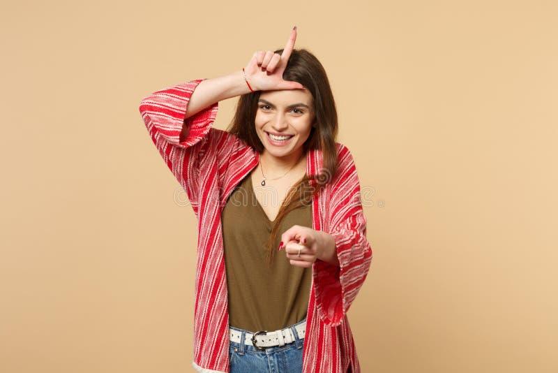 Jeune femme riante dans des vêtements sport montrant le geste de perdant, dirigeant l'index sur la caméra d'isolement sur le beig images stock