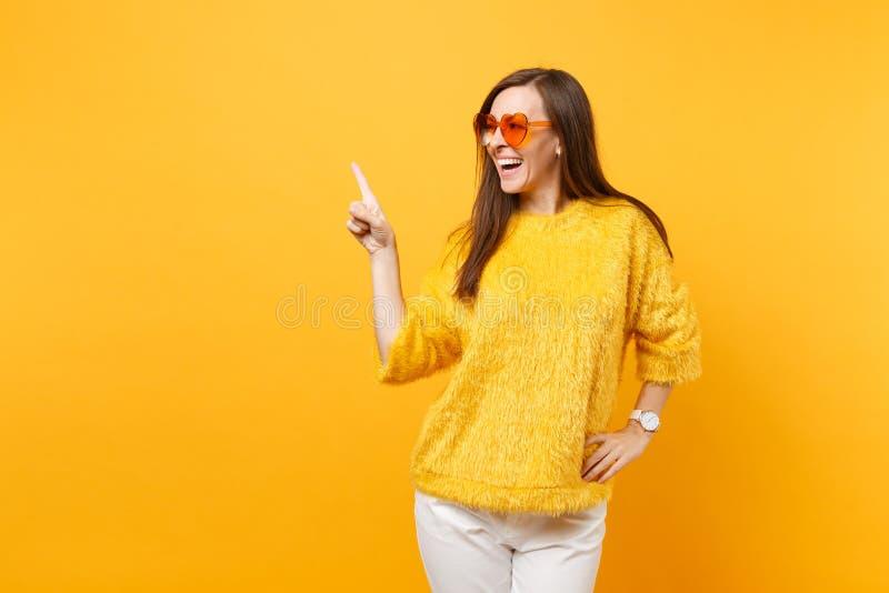 Jeune femme riante dans le chandail de fourrure, verres oranges de coeur dirigeant l'index de côté sur l'espace de copie d'isolem photo stock