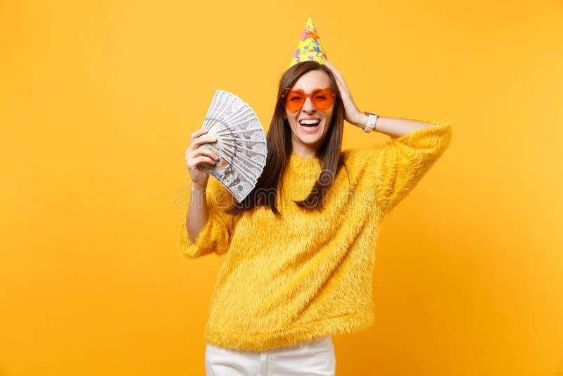 Jeune femme riante dans le chapeau orange d'anniversaire en verre de coeur mettant la main sur un bon nombre de paquet de partici photo libre de droits