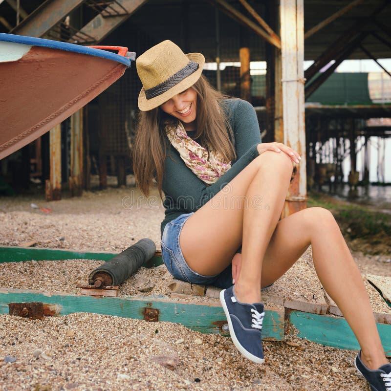 Jeune femme riante drôle avec de longues jambes regardant sur ses chaussures en caoutchouc sous le vieux pilier photos stock