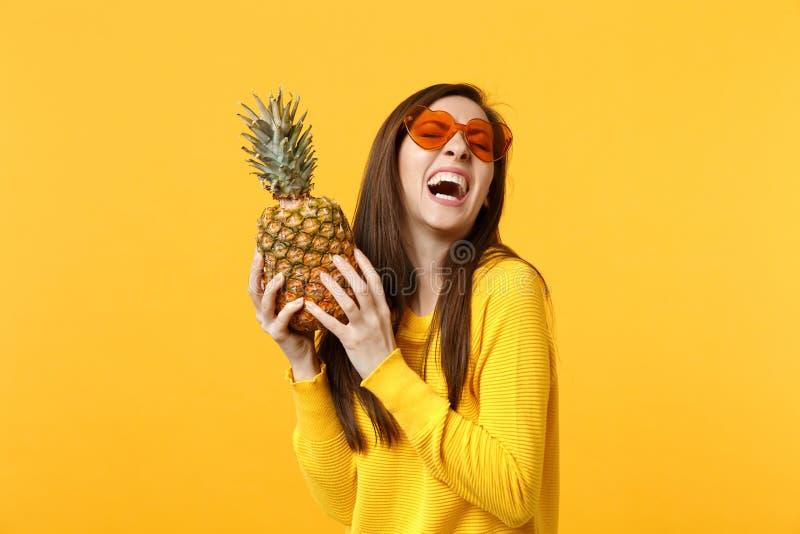 Jeune femme riante en verres de coeur se tenant en fruit mûr frais d'ananas de mains d'isolement sur le fond jaune-orange image libre de droits