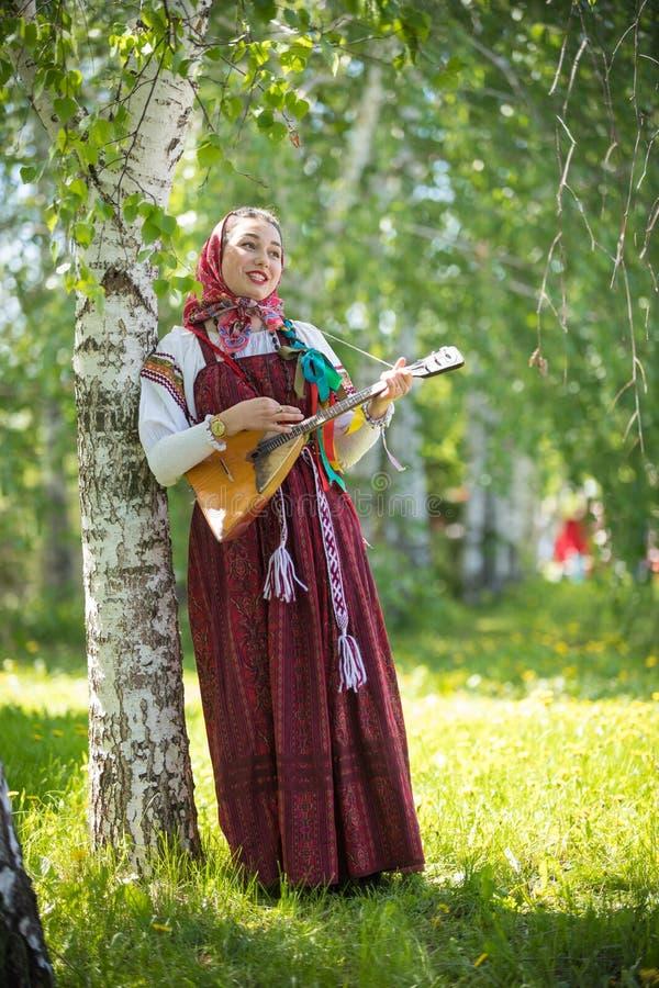 Jeune femme romantique dans des v?tements russes traditionnels se tenant dans la for?t et tenant la balala?ka image stock
