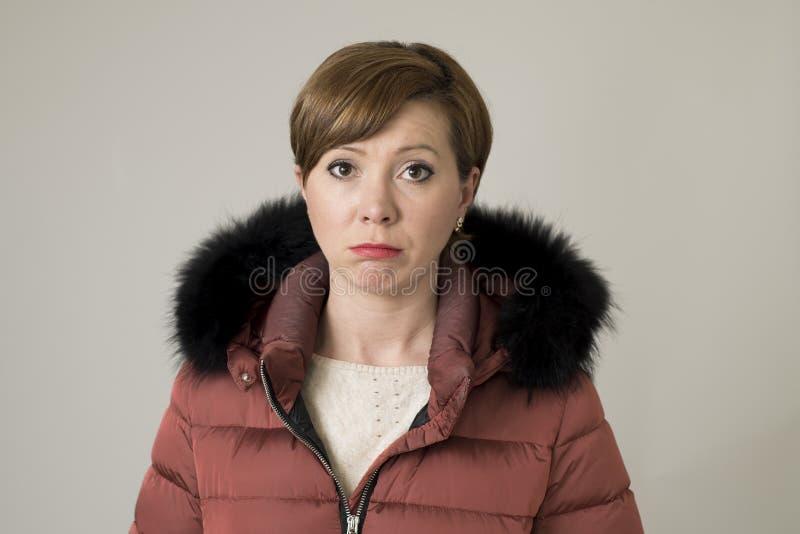 Jeune femme rouge douce et triste de cheveux posant le regard déprimé et déprimé à l'appareil-photo utilisant la veste chaude de  photo stock