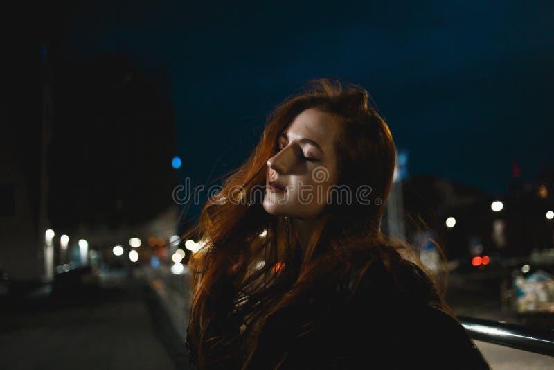 Jeune femme rousse élégante posant dans la ville de nuit image libre de droits
