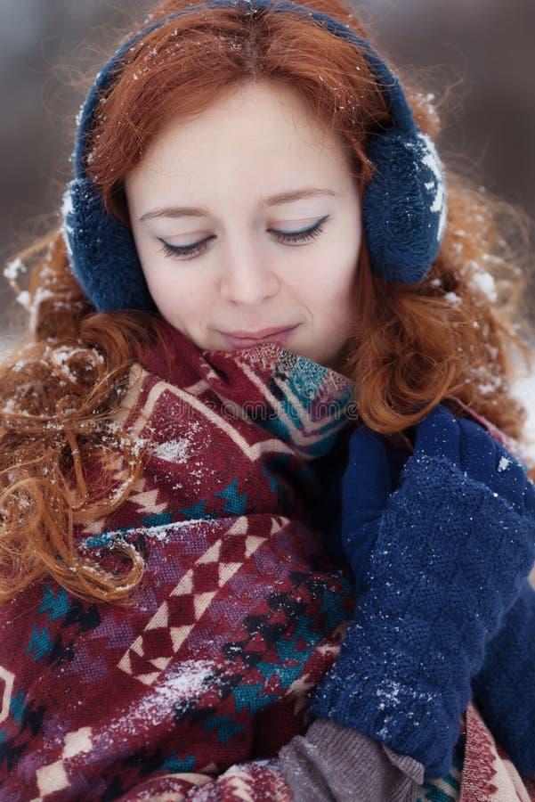 Jeune femme rousse attirante avec la neige dans ses cheveux image stock
