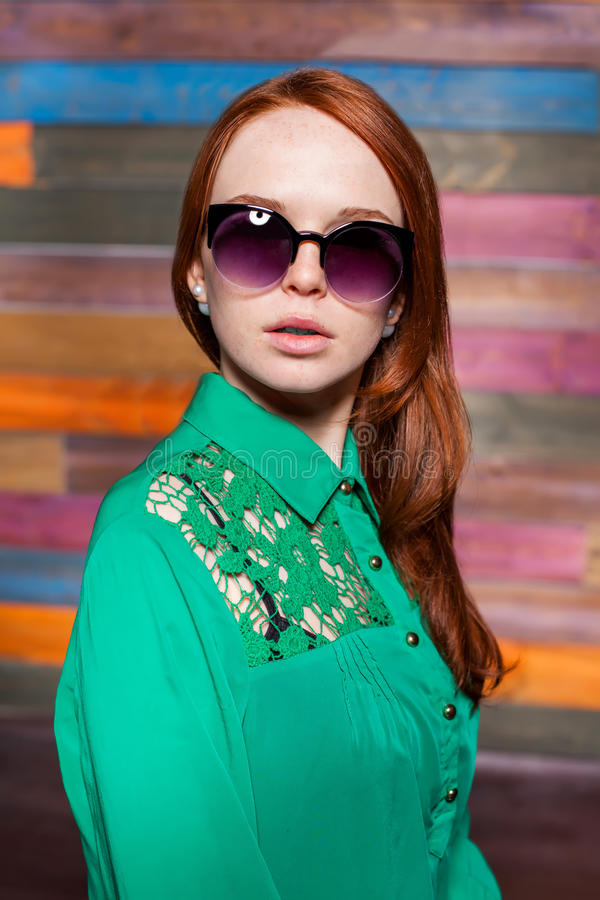Jeune femme rousse attirante dans des lunettes de soleil photographie stock libre de droits