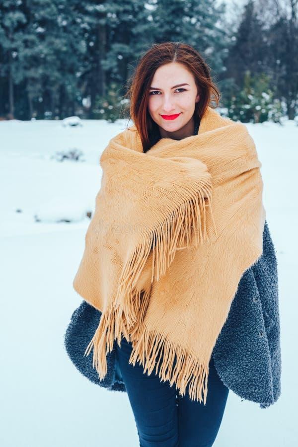 Jeune femme rousse avec une écharpe rouge dans une forêt d'hiver images libres de droits