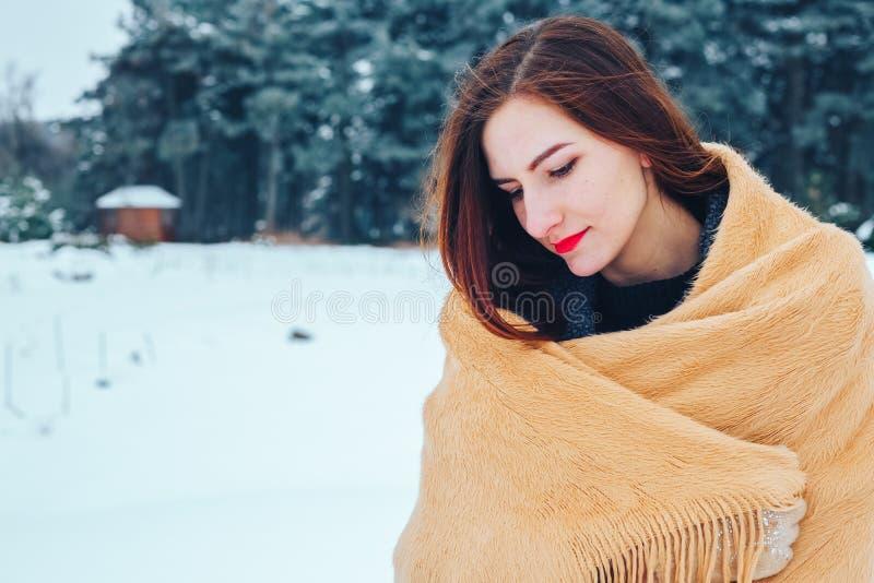 Jeune femme rousse avec une écharpe rouge dans une forêt d'hiver photographie stock libre de droits
