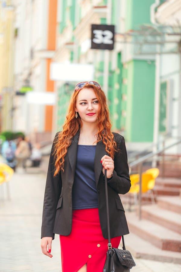 Jeune femme rousse d'affaires descendant la rue photos libres de droits